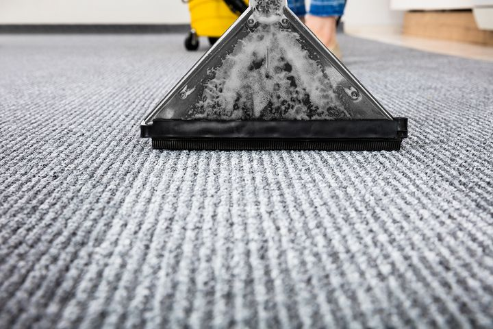 צילום מקרוב של ניקוי שטיח באמצעות שואב אבק